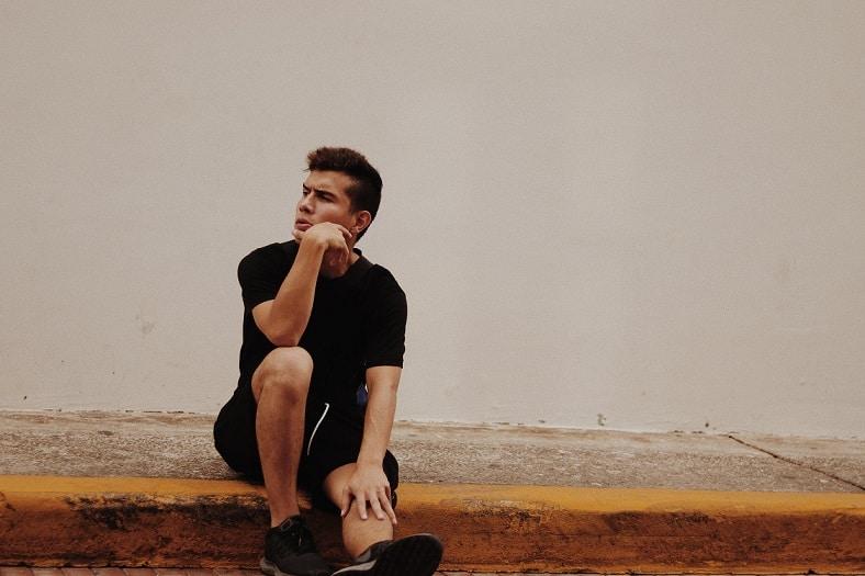 בחור צעיר יושב וחושב על המסקנות שהוא הסיק מקריאה של מאמר