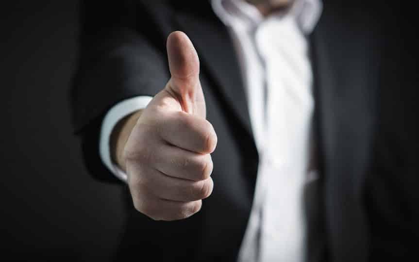 גבר בחליפה שחורה עושה סימן עם האצבע שהכל בסדר ויהיה טוב