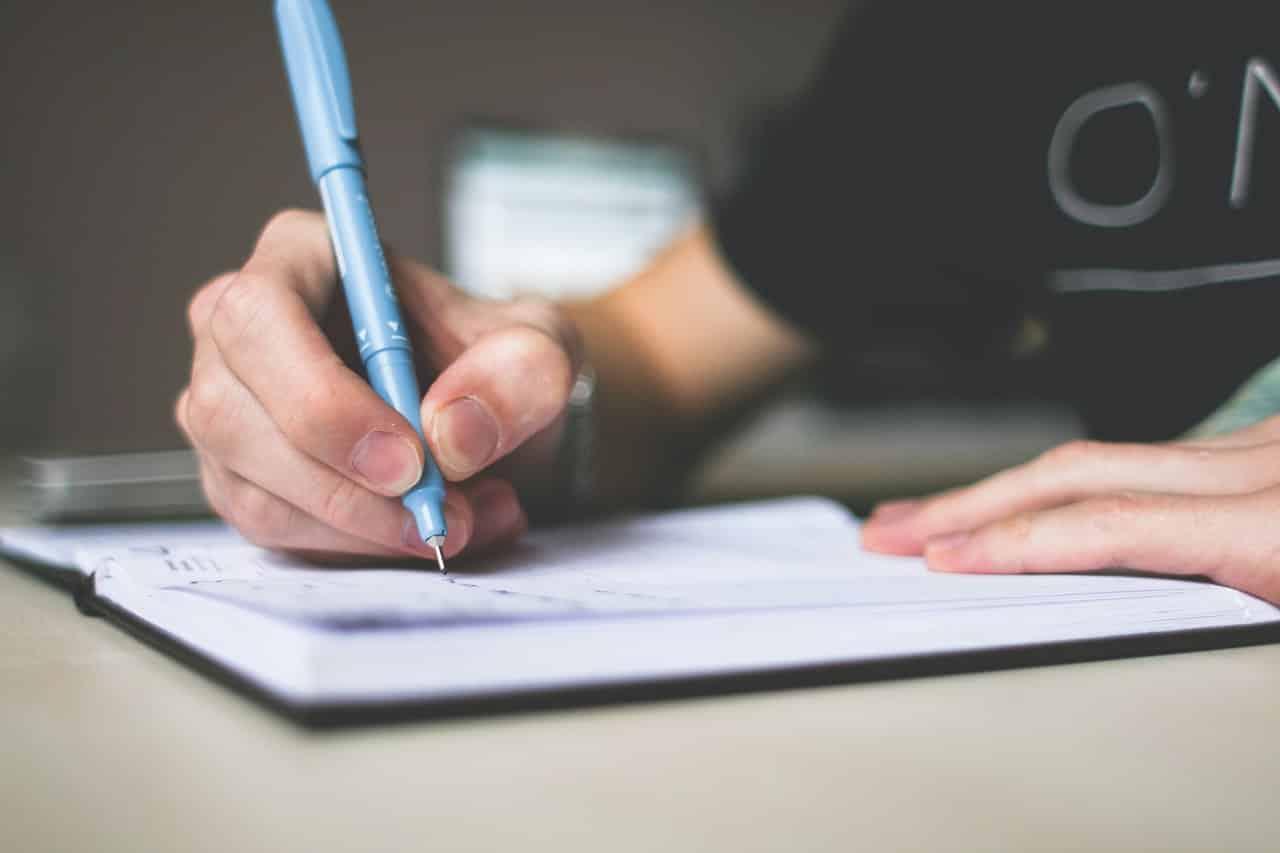 יד של גבר רושמת דברים ביומן עם עט כחול ישן