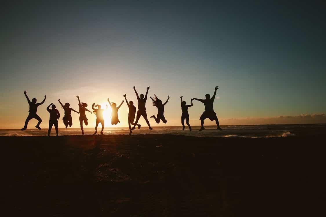 אנשים שמחים קופצים על חוף הים אל מול השמש השוקעת