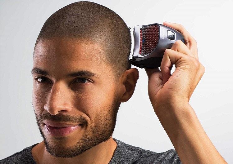 גבר מגלח את הראש עם מכונת התספורת לגילוח הראש של רמינגטון