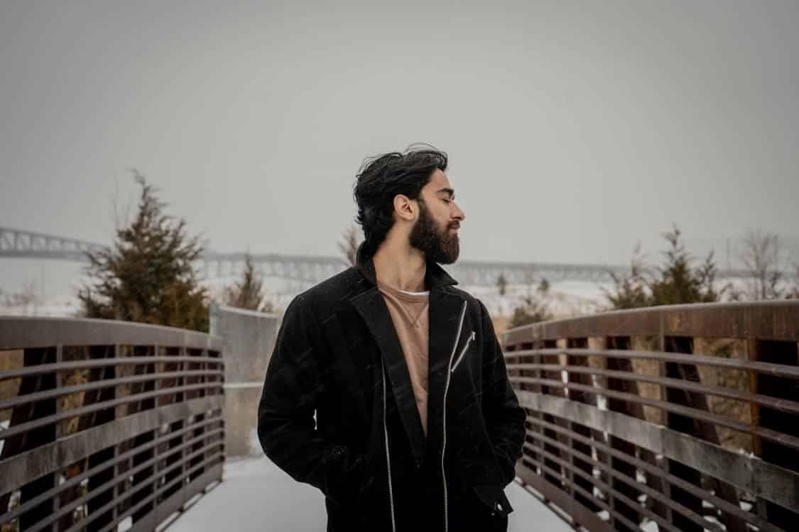 גבר עם שיער ארוך על גשר ומבט מאוד מרוצה