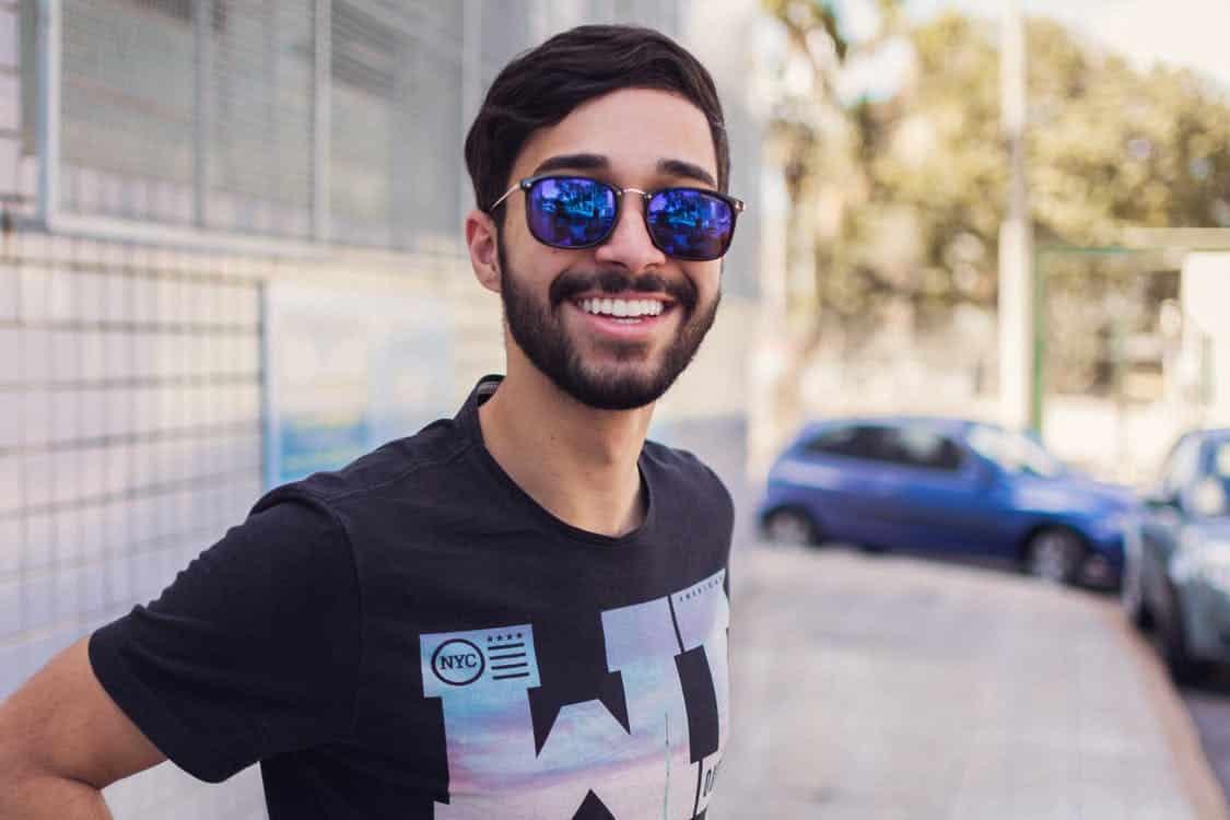 גבר צעיר במשקפי שמש מסתכל ומחייך למצלמה