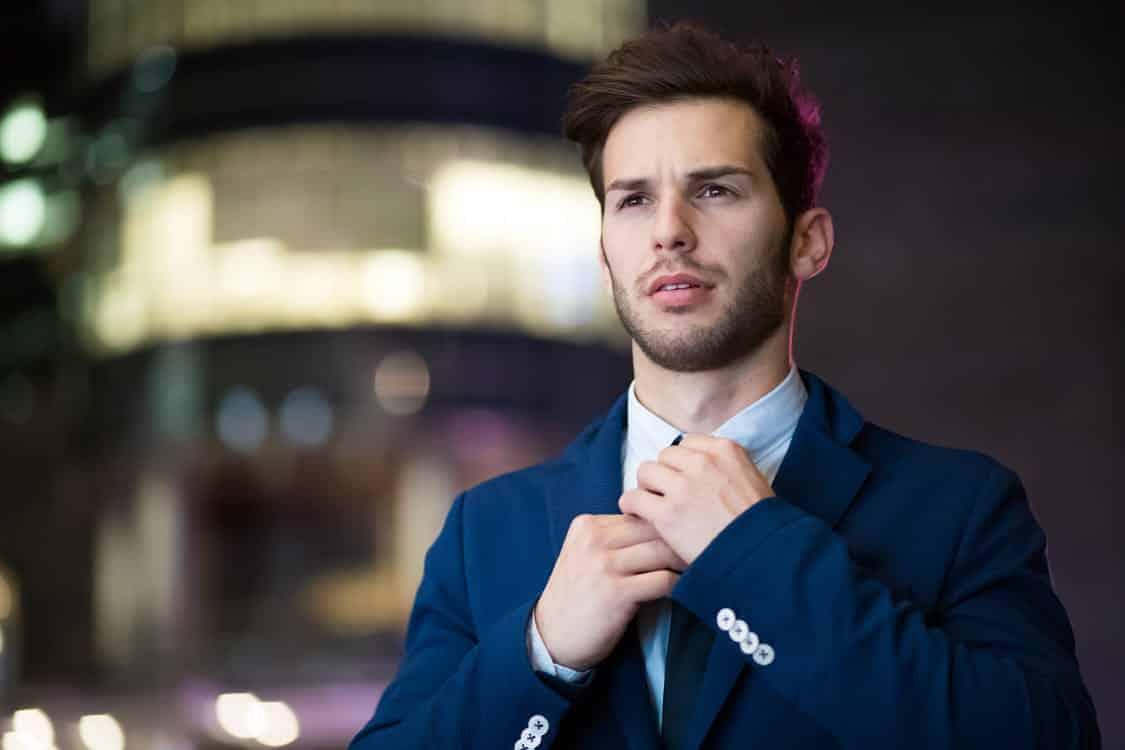 גבר צעיר ומגולח בחליפה כחולה מצטלם ברחוב