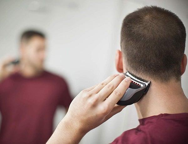 גבר צעיר משתמש רמינגטון HC4250 כדי לגלח את הצד האחורי של הראש
