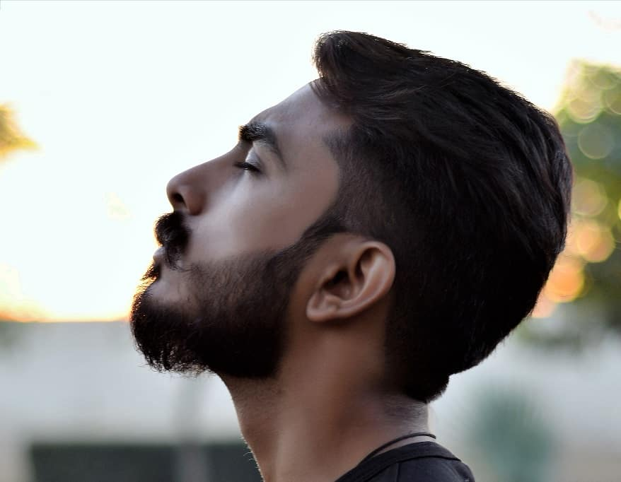 גבר צעיר עם תספורת אופנתית ומדוייקת עוצם עיניים