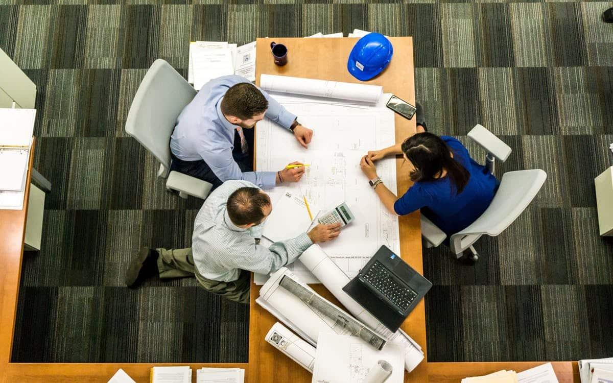קבוצה של אנשים יושבים מסביב לשולחן ומפתחים טכנולוגיה חדשה
