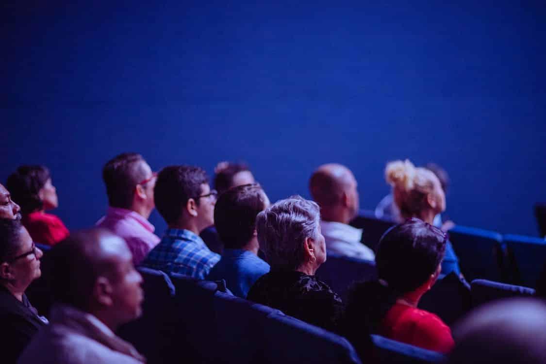 תמונה של אנשים שיושבים באולם בזמן תערוכה