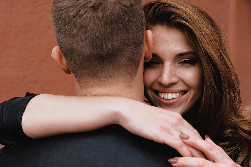 אישה מחבקת בחור ומחייכת למצלמה