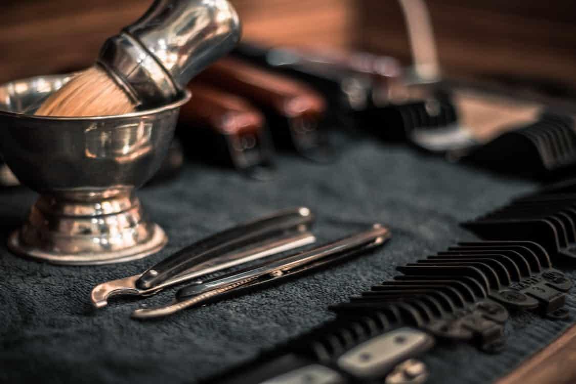 אביזרי גילוח שונים מונחים על שולחן במספרה
