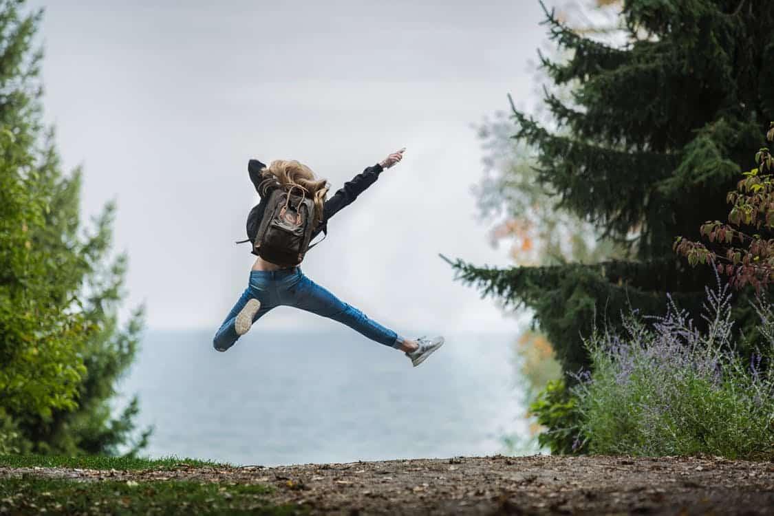 אישה צעירה קופצת מאושר בטבע תמונה אחורית