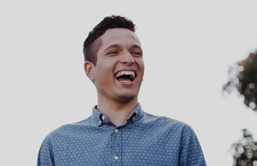 בחור צעיר ומגולח מחייך חיוך ענק ומסתכל לצד ימין
