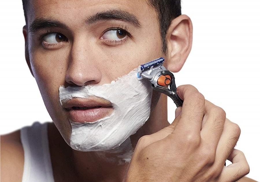 גבר מתגלח עם סכין גילוח רב פעמים של ג'ילט