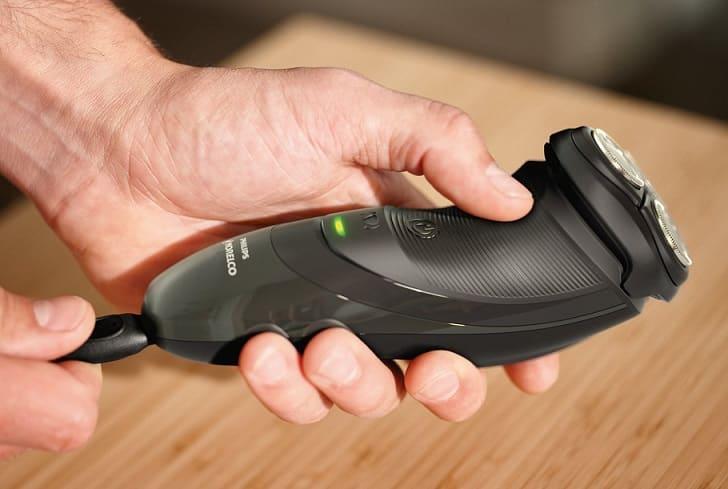 יד מחזיקה מכונת גילוח רוטורית על רקע של עץ
