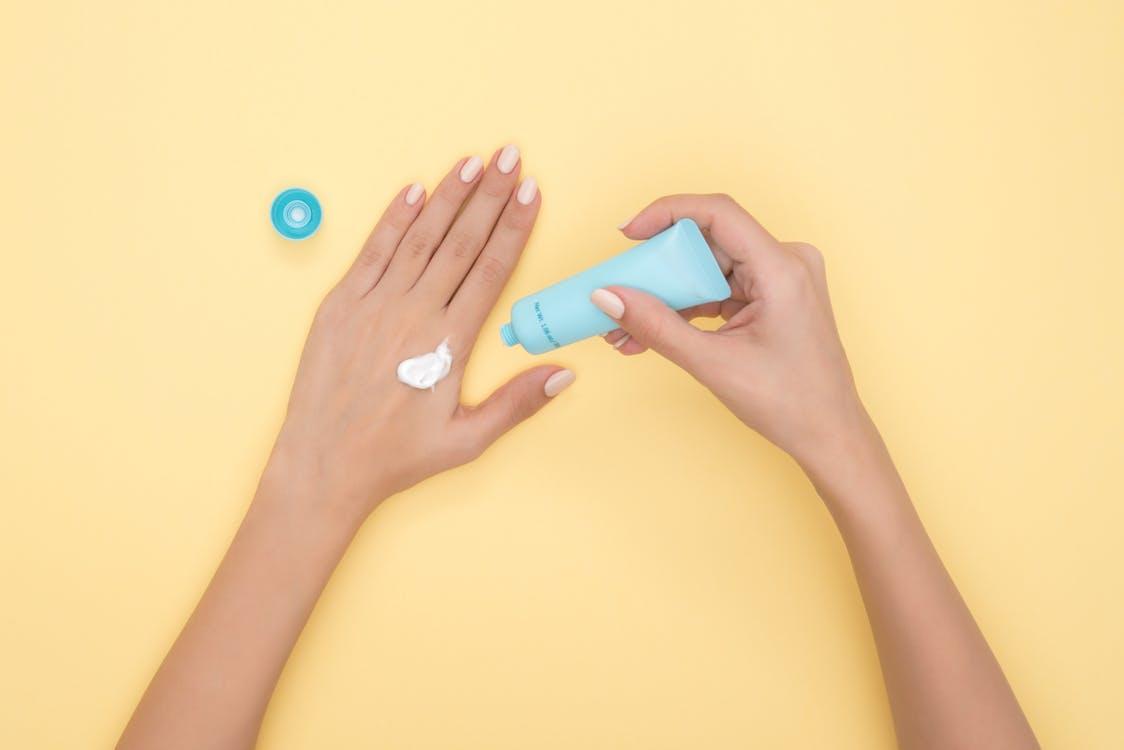 על רקע צהוב ידיים של אישה משתמשות בקרם לחות