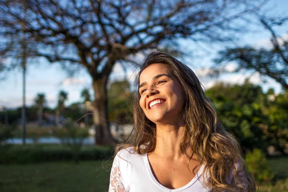 בחורה צעירה מחייכת ומטיילת בפארק באמצע היום